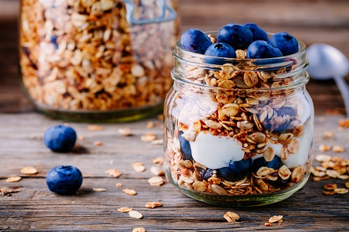 Healthy breakfast parfait with yogurt, homemade granola and fresh bluberries in glass jar